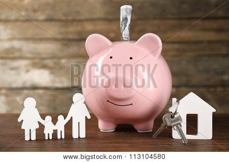Pig money box and paper decor on wooden wall background