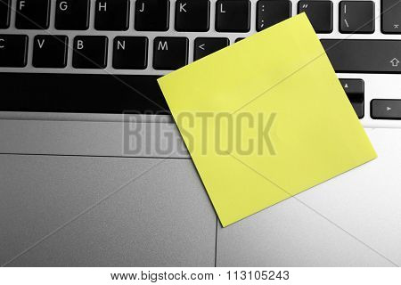 Empty yellow adhesive paper on laptop keyboard, on light background