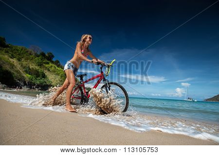 Woman walking with bicycle on the tropical beach