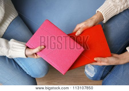 Woman giving book to woman, on wooden table background