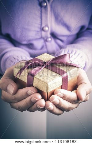 Close up of hands holding a small gift wrapped with purple ribbon. Small gift in the hands of a woman indoor. Shallow depth of field with focus on the little box.