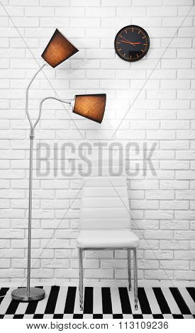 Modern chair and lamp on brick wall background