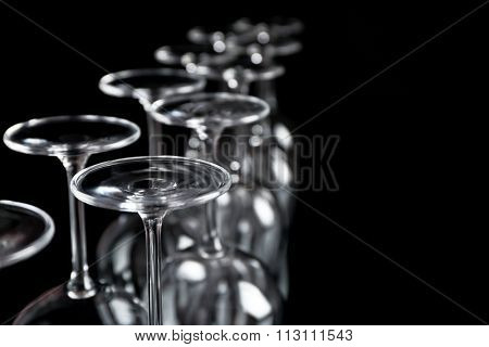 Wine glasses in a row upside down on black background