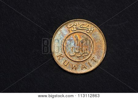 Ten fils Kuwaiti Dinar coin close up on black background.