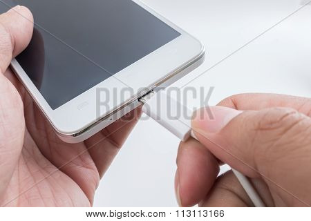Hand Holding White Smart Phone And Plugging In Usb Cable Over White Background