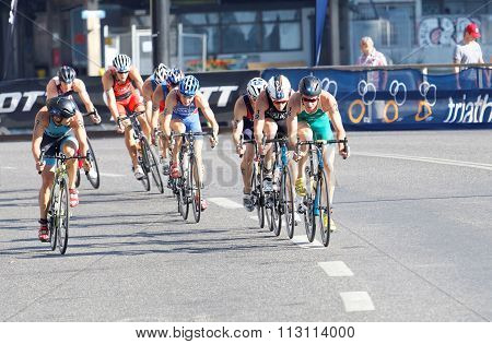 Large Group Of Colorful Triathletes Cycling In A Curve