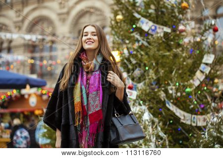 Young beautiful woman in stylish mink coat on a background of a winter street