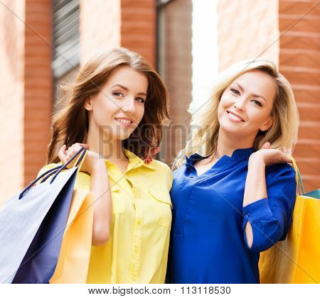 Portrait of two gorgeous shopaholics being emotional with shopping bags in city center.