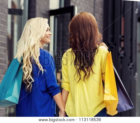 Two happy shopaholic ladies walking with shopping bags in city center.