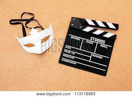 White Mask And Movie Clapper On Cork Wooden Background