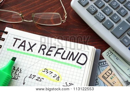Notebook with tax refund sign on a table.