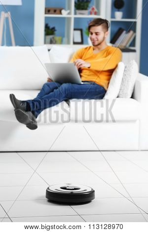 Cleaning concept - automatic robotic hoover clean the room while man relaxing with laptop, close up