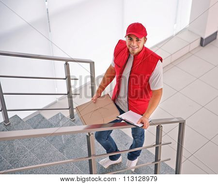 Delivery concept - postman in red uniform rising on stairs with package