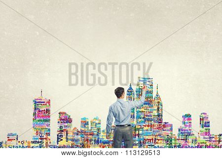 Back view of businessman writing leadership concepts on wall