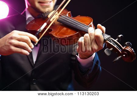 Violinist's performance on black background, close up