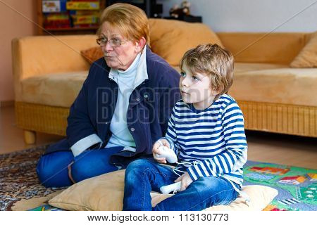 Little kid boy and grandmother playing video game console