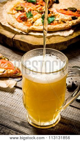 The Breath Of Fresh Beer Being Poured Into Glass. On The Background Of The Pizza.