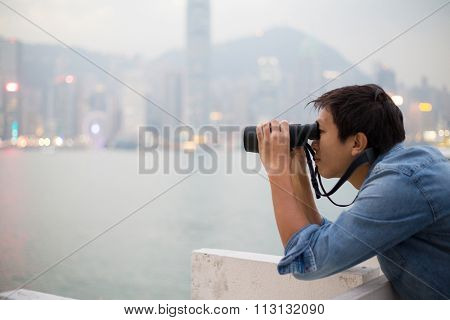 Asian Man looking though binoculars at Hong Kong