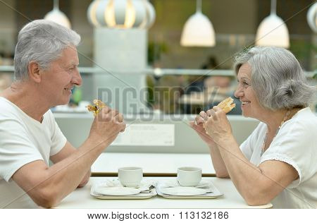 beautiful elderly couple eating fast food