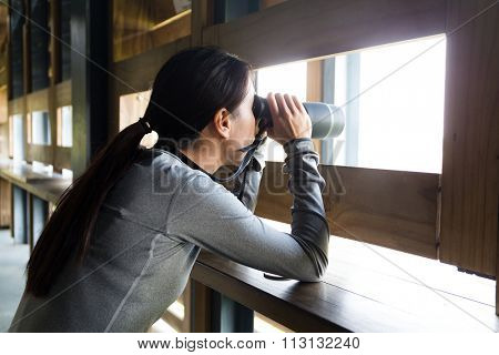 Asian Young woman looking though binoculars for birdwatching