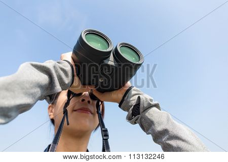 Woman watching though binoculars with clear blue sky