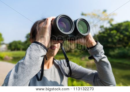 Asian Young woman watching though binoculars at forest