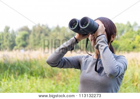 Asian Young woman watching though binoculars