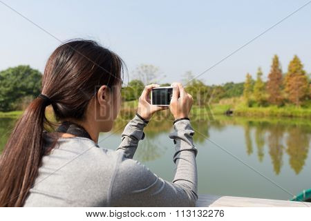 The back view of Young woman taking picture by digital camera