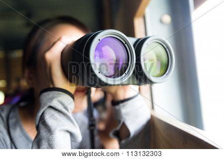 Young woman using binoculars for birdwatching
