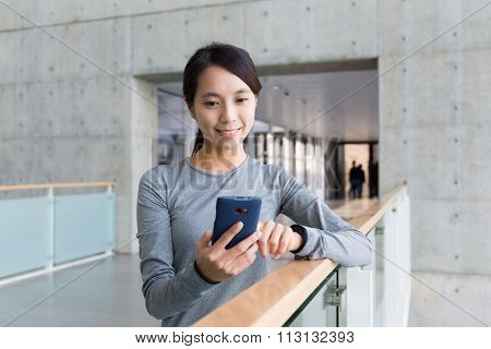 Woman checking the text message outside office