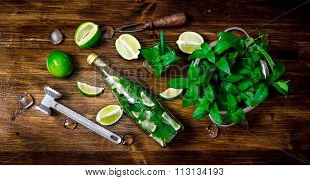 Ingredients For Cooking - Limes, Mint Leaves, Hammer, Rum On The Wooden Background.