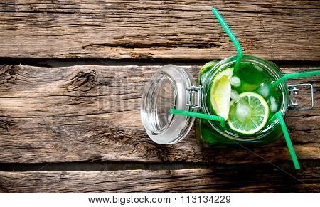 Mojito In A Jar With 4 Tubes On A Wooden Table.