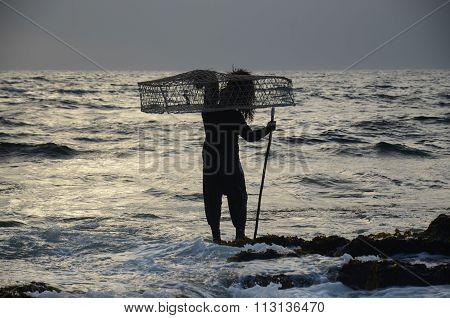 Fisherman in Oman carrying basket