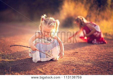 Little girl playing in the dirt with a stick