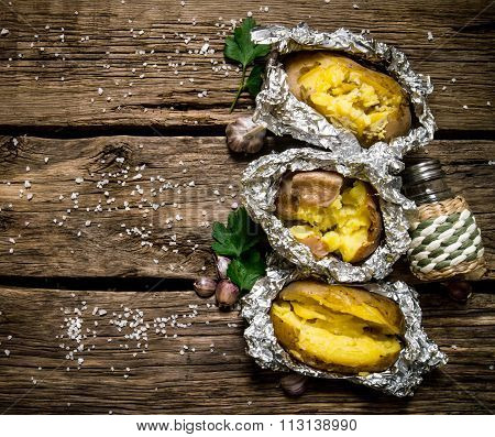 Baked Potatoes In Foil On A Wooden Table . Free Space For Text.