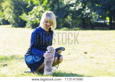 Young blonde asking her dog to sit