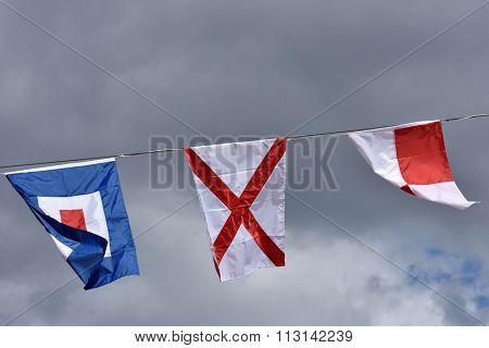International maritime signal flags Uniform, Victor, and Whiskey against cloudy sky