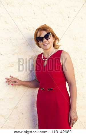 Mature woman in red dress smiles broadly