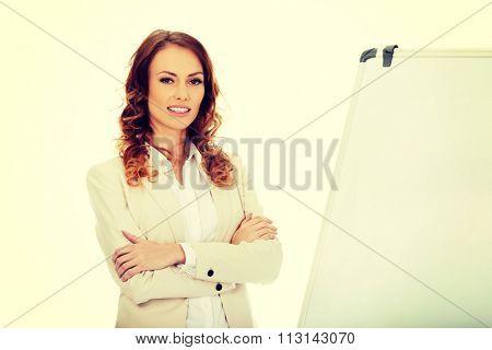 Smiling business woman near flipchart.