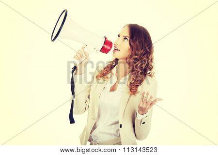 Beautiful businesswoman shouting with megaphone.