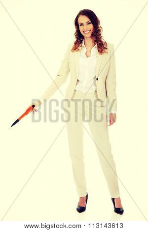 Attractive businesswoman pointing down with oversized pen.