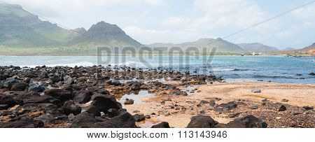 Black rock stone sand beach coast in front of blue sea with mountain background