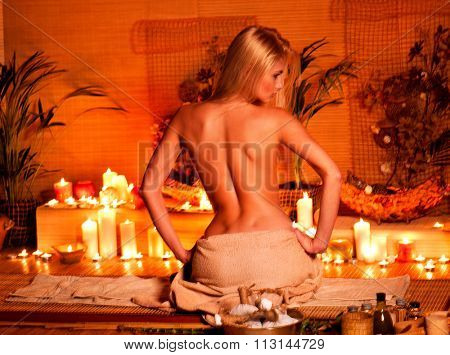 Young woman getting massage in bamboo spa. Back view.