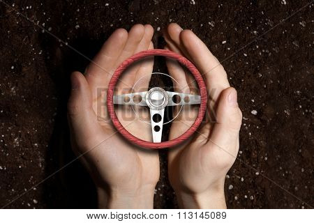 Hands of man holding with care car steering wheel