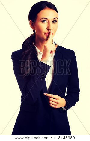 Beautiful businesswoman making silent sign.