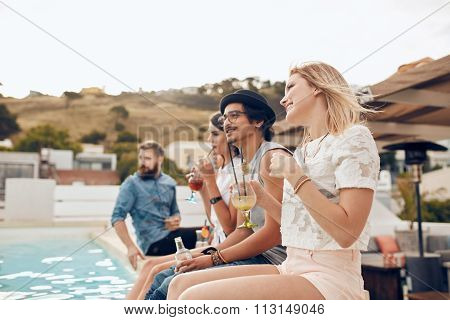 Happy Young Friends Sitting By The Pool Having Drinks