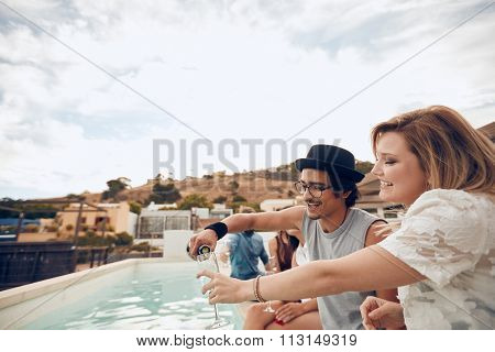 Friends Having Drinks At Party By The Poolside