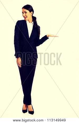 Smiling businesswoman holding copyspace on the left hand.