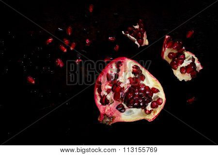 Pomegranate And Pieces Of Ripe Pomegranate With Grains On A Dark Background