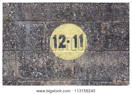Black Numbers In A Yellow Circle Painted On Dark Brickwork Wall In The Outdoors With A White Frame